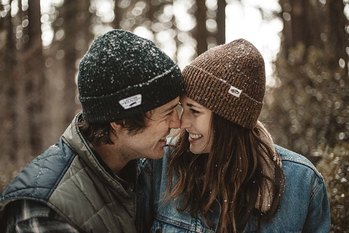 A smiling joyful couple in the snow - smile for the camera