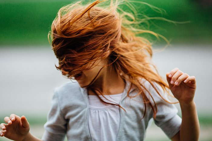 Fun portrait of a laughing female model tossing her auburn hair - how to smile for pictures