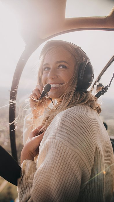 A joyful photo of a blonde woman in an aircraft smiling naturally