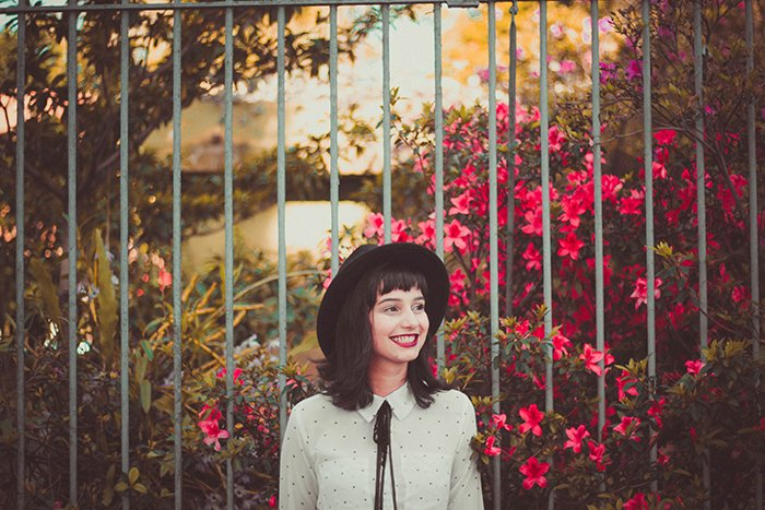 A female model standing outdoors in front of flowers and smiling naturally - how to smile in pictures