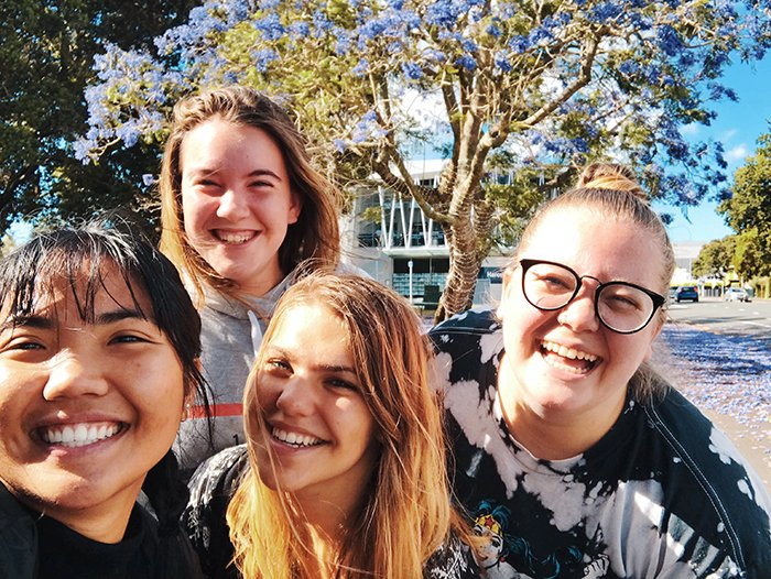 A group selfie of smiling people outdoors
