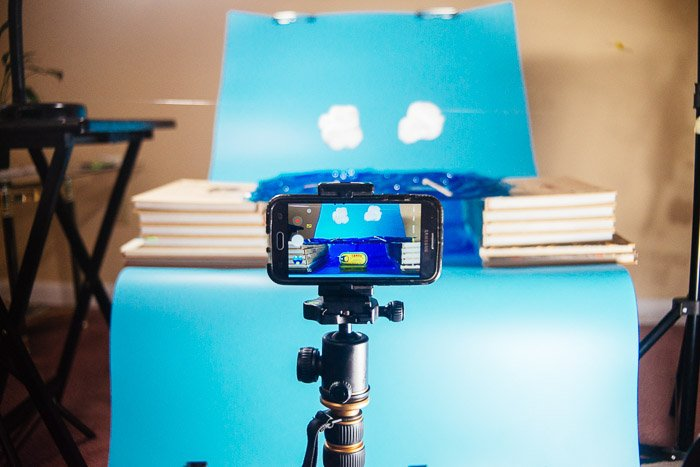 A phone set up on a tripod for someone to shoot smartphone product photography