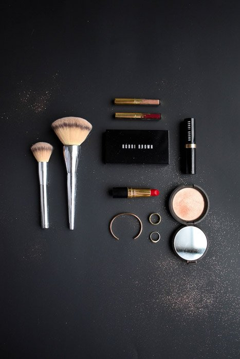 Flatlay product photography businesst shot of cosmetics on a dark background