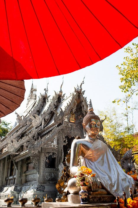 A statue of buddha under a red umbrella in front of a temple - how to remove glare in photos