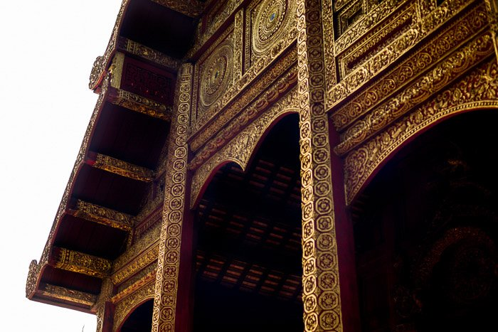 The exterior of an ornate gold temple - how to remove glare in photos