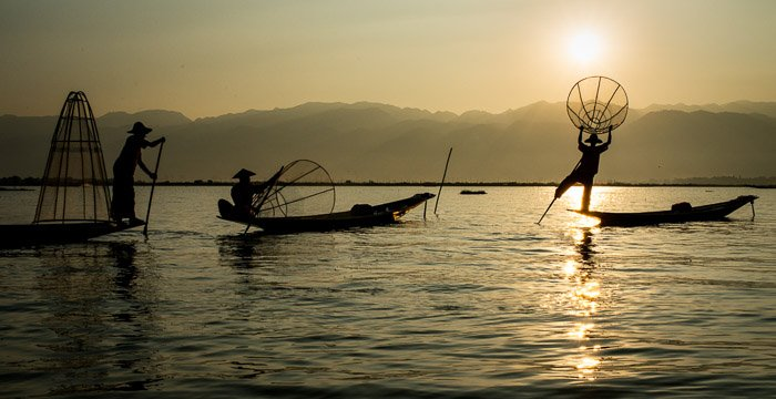 Serene shot of fishermen in a lake at sunset after removing glare in photos