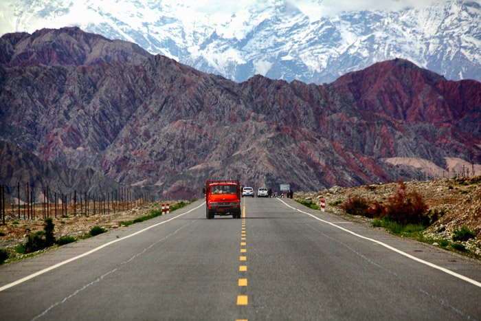 a red truck driving on a highway, a beautiful; mountainous landscape in the background - rule of space in photography