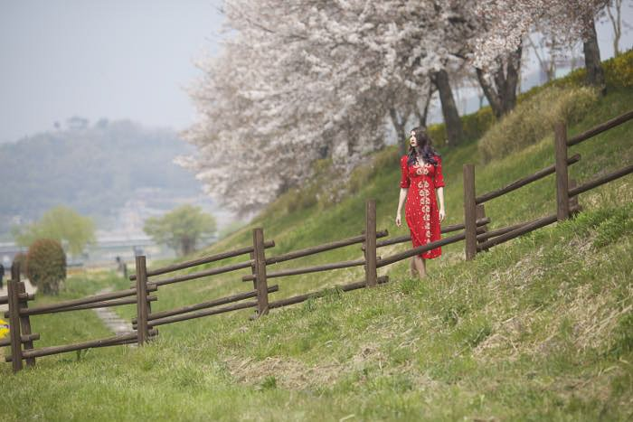 A female model in red dress walking through country fields - rule of space photography