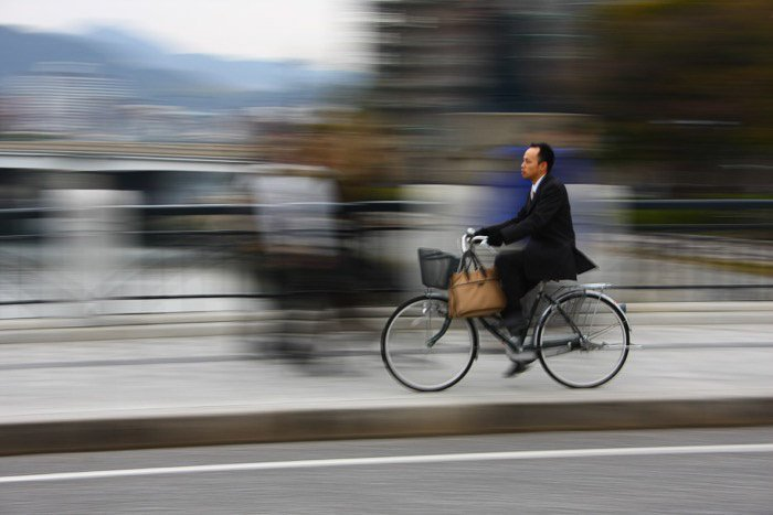 A man riding a bicycle in a cityscape with motio0n blurred background - rule of space photography