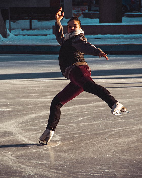 Cool ice skating photography of a female skater twirling on the ice
