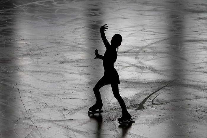 Beautiful figure skating photography of the silhouette of a female skater on the ice