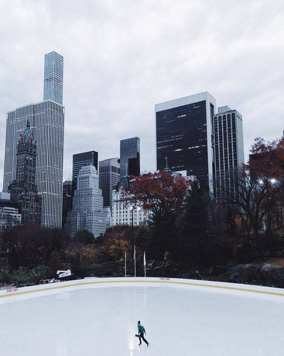 n outdoor ice skating rink beneath tall skyscrapers