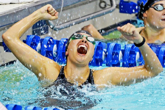 An action shot of a female swimmer celebrating victory after a race - how to take swimming pictures