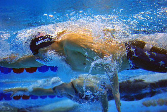 An underwater action shot of swimmers in a pool - how to take swimming pictures