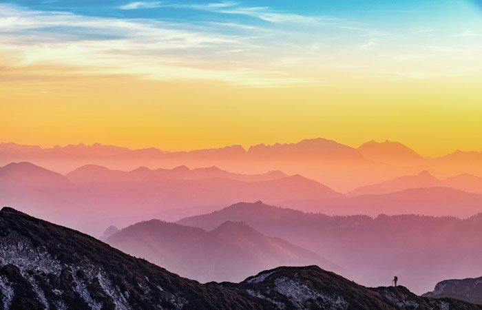 A mountainous landscape under a colorful sunset sky - color theory for landscape