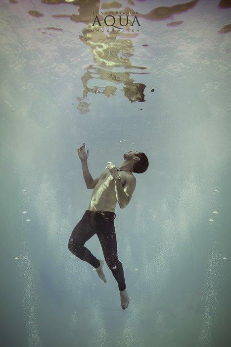Atmospheric underwater photoshoot of a male model posing underwater