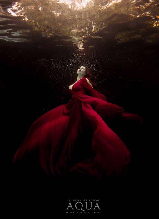 Atmospheric underwater photoshoot of a female model in a red dress posing underwater