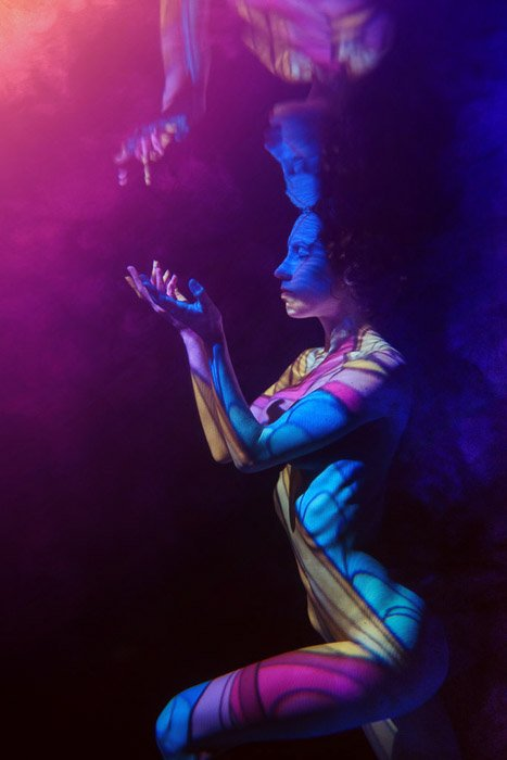 Artistic underwater photoshoot of a female model surrounded by colored light posing underwater