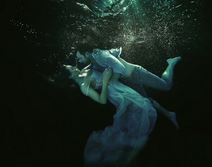 Atmospheric underwater photoshoot of a couple embracing underwater
