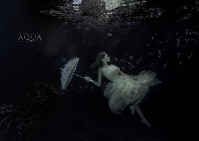 Atmospheric underwater photoshoot of a female model holding an umbrella underwater