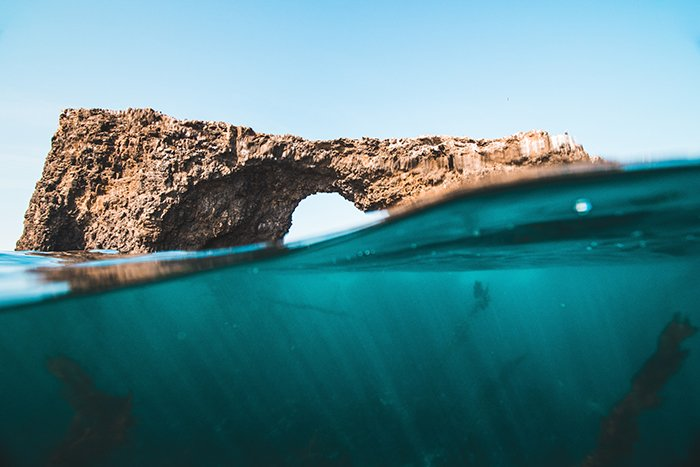 A half-above, half-below underwater photo of a rock formation in the sea