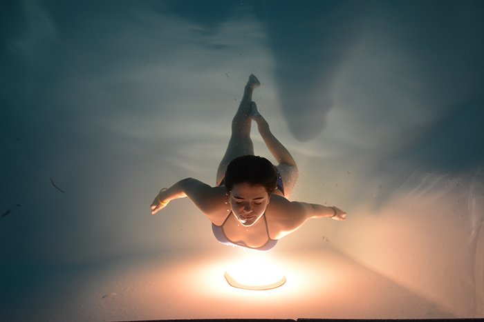 a stunning underwater portrait of a female swimmer posing over a warm light