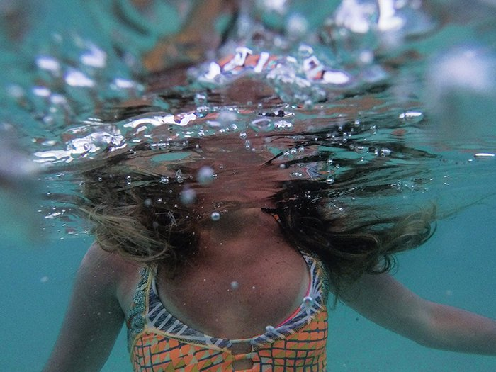 Atmospheric underwater photo of a female swimmer