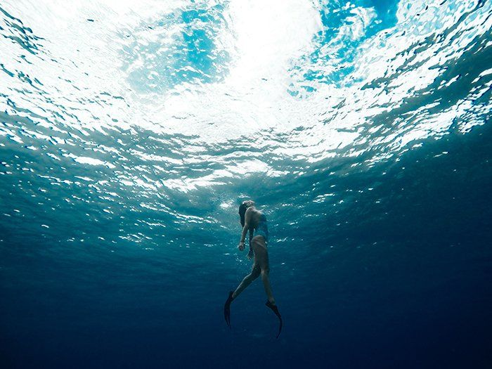 Cool underwater portrait of a girl swimming towards the surface