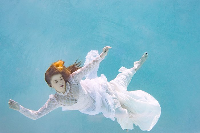 ethereal underwater portrait of a female swimmer in a long, flowy dresses look