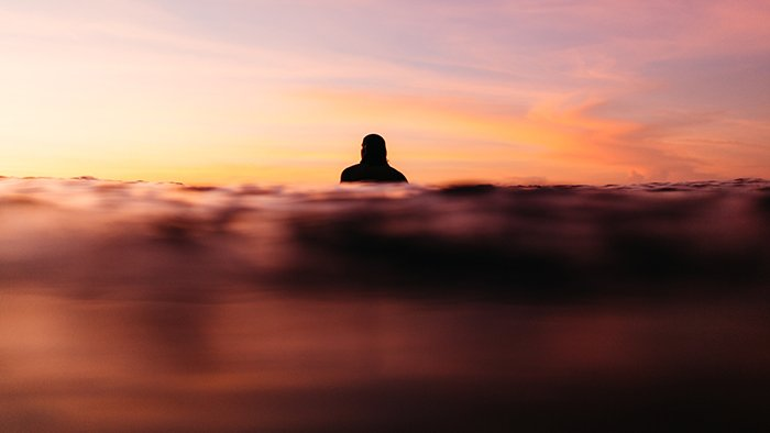 Dreamy photo of the silhouette of a swimmer shot during golden hour