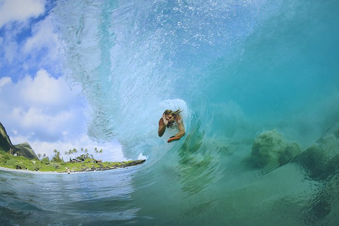 A professional surfer riding a large wave - underwater photography tips