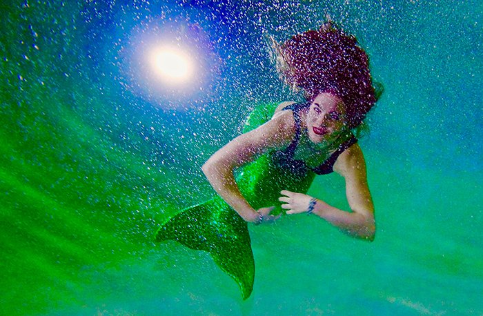 Colorful mermaid photography shoot of a female model swimming underwater