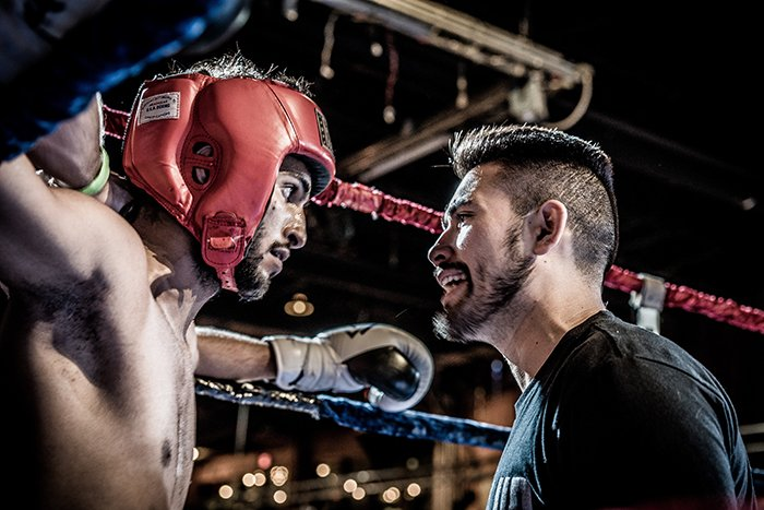 Atmospheric boxing pictures of a fighter talking with a trainer during a boxing match