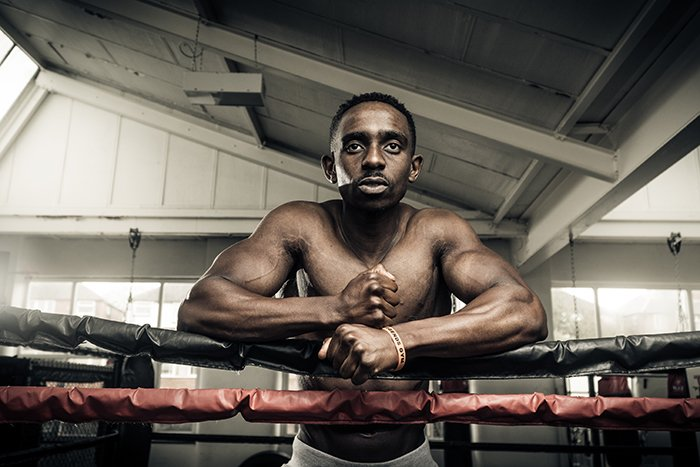 Atmospheric boxing photography of a fighter leaning against the ropes in a gym