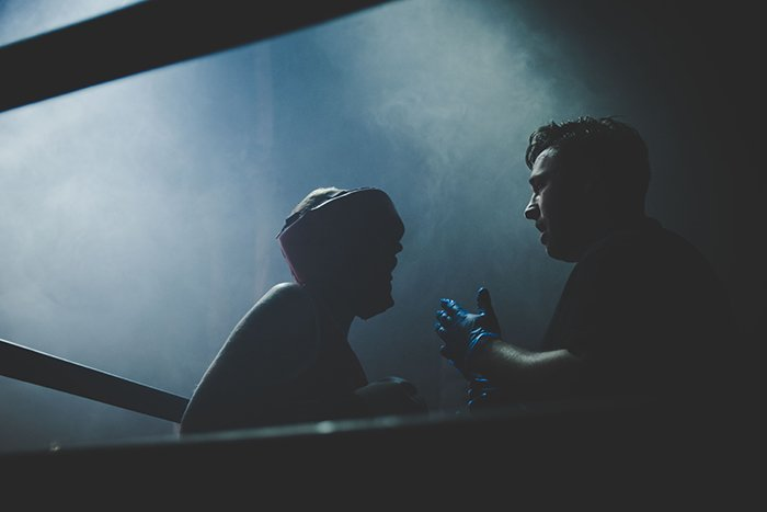 Atmospheric boxing pictures of a fighter and trainer shot through the boxing ring ropes to create depth
