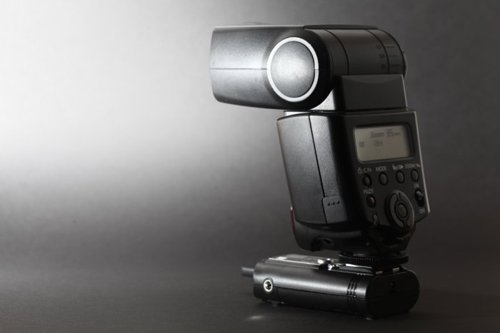 an old Canon 430EX II fires a flash at a black background - best camera flash
