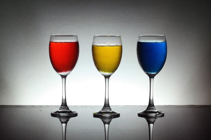 A product shot of three wine glasses with red, yellow and blue liquid inside - best camera flash