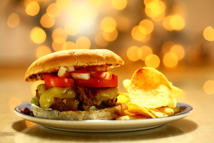 A delicious shot of a juicy burger and chips - camera flash photography