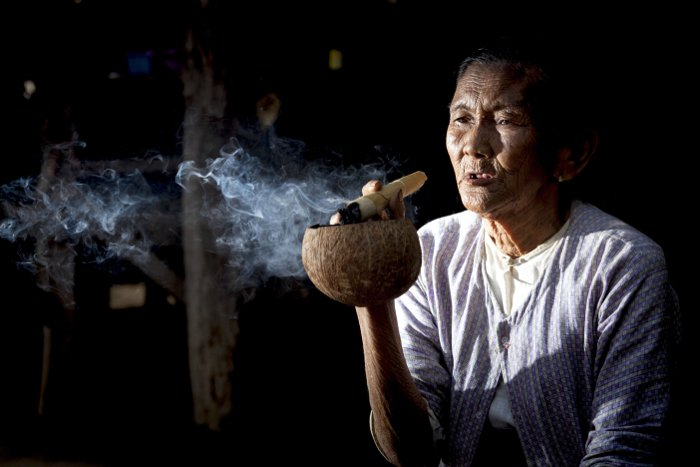 a low key portrait of an old woman smoking shot used a flash to the left of the camera