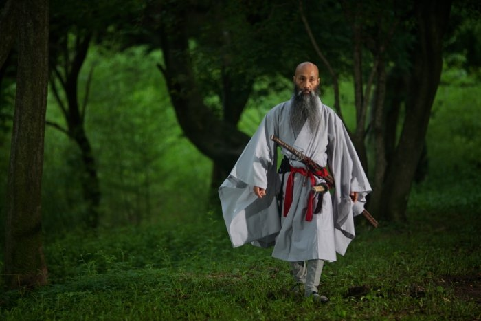 Atmospheric portrait of a monk lit by strobes in the dimly lit forest.