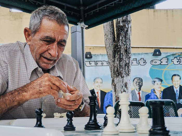 An old man playing chess outdoors