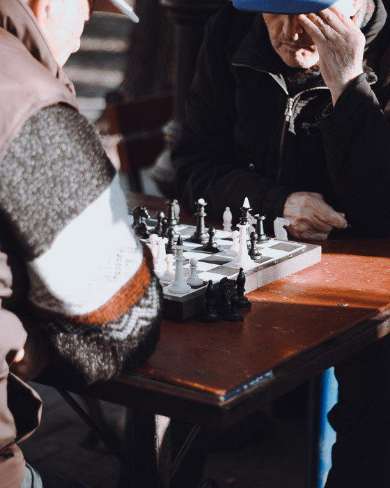Candid chess photography of two men playing a game of chess outdoors