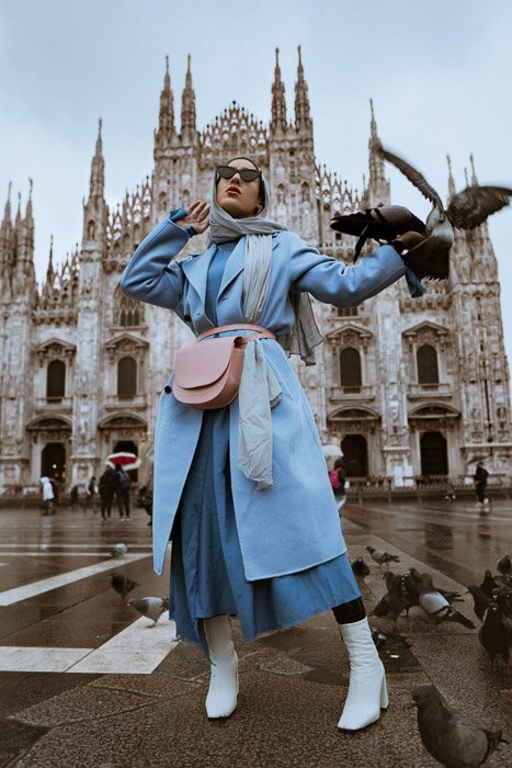 A female fashion model posing in front of a historical building with pigeons flying around her - fashion lookbook tips