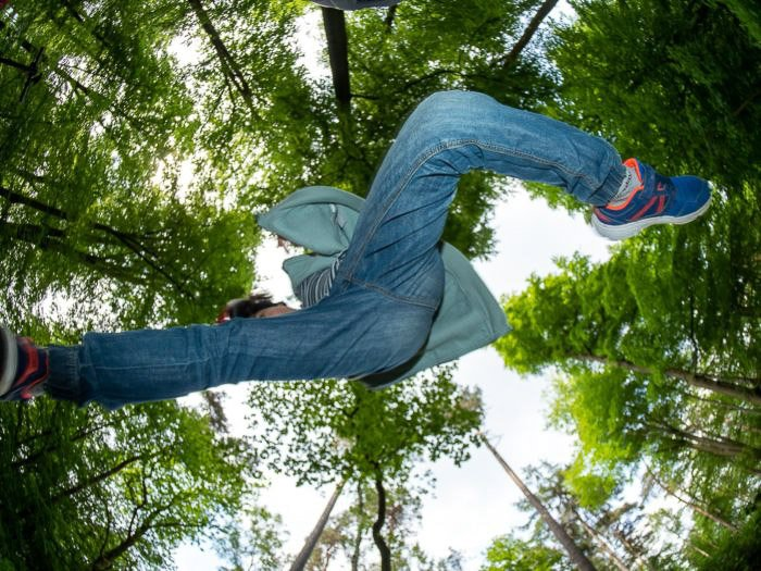 Cool fisheye photos of a child jumping in a forest