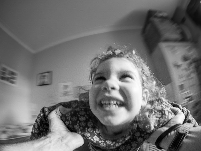 Black and white portrait of a smiling child shot with a fisheye lens