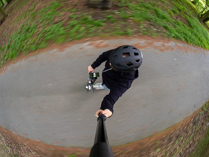 A fisheye lens selfie taken while riding an electric kick scooter in the forest.