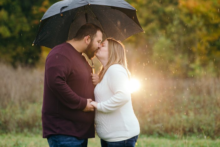 Outdoor portrait of a couple kissing under an umbrella