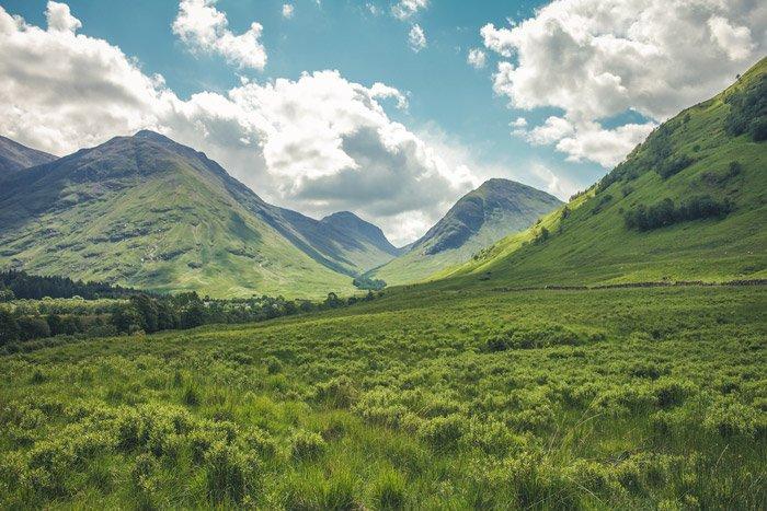 a luscious green mountainous landscape under a cloudy sky - stunning landscape photos