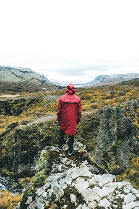 a photographer standing on a rocky in a mountainous landscape - Iceland photography spots