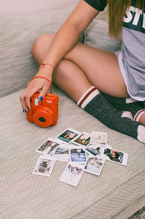 A girl with an instant camera looking over instant photos